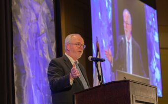 Morgantown Partnership President & CEO Russ Rogerson speaks animatedly with his hands up at a podium at the Partnership's Annual Dinner event.