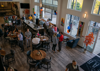 aerial of large event room with cocktail tables and large windows, people gathered in small groups networking at the bar and around the room