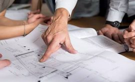 Hand pointing at blueprint of a building
