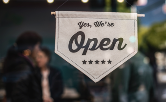"""Cloth sign on storefront that depicts """"Yes, we're open."""" Patrons of the store are blurred out in the background."""