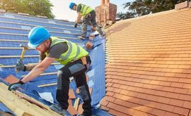 Two construction workers fix the roof of a house