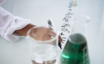 scientist writing mathematical equation on table with beakers