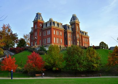 Woodburn Building at WVU on the hill in the fall, surrounded by trees and blue sky